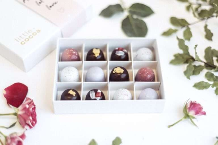 open box of 12 pralines with a pink theme displayed with pink roses