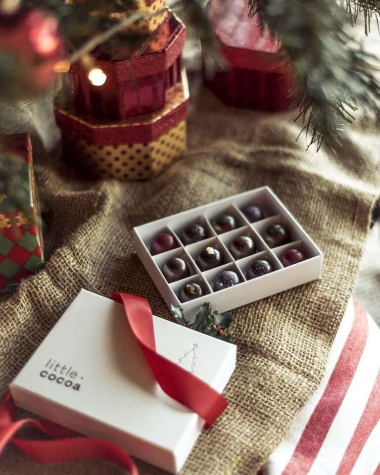 12 chocolate pralines in an open white box displayed under a christmas tree