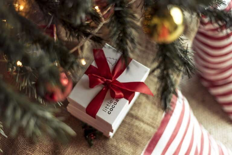 a white box of chocolates secured with a bold red ribbon displayed under a christmas tree