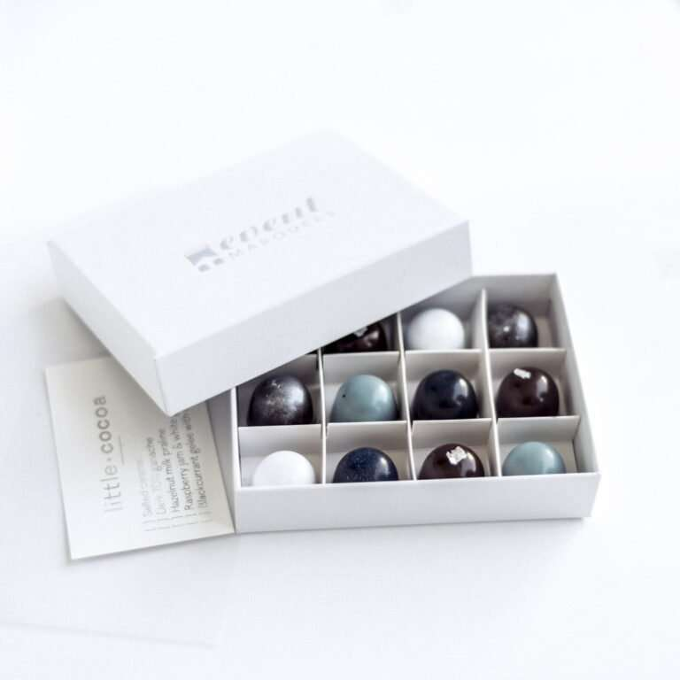 12 chocolate pralines with a silver-grey theme displayed in an open white box embossed in silver foil with a label that says 'Event Marquees'