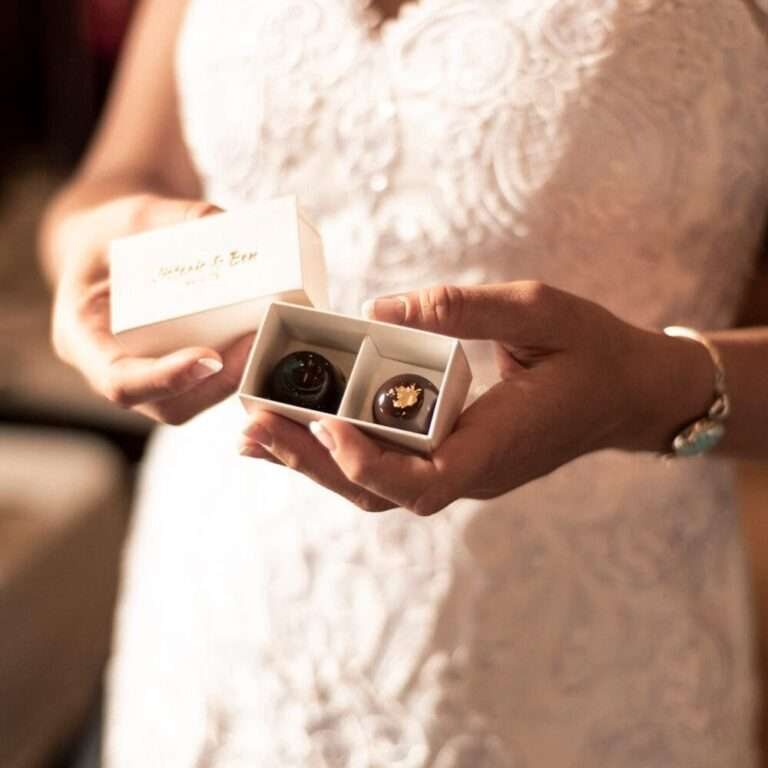 two piece box of chocolates with lid removed held in hand by bride