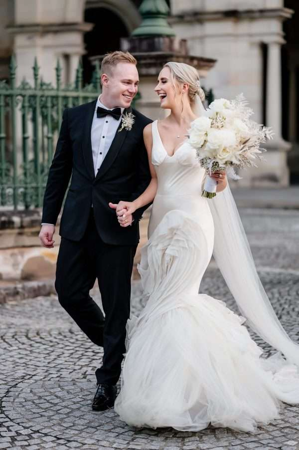 bride in white gown holding a white flower bouquet and groom in a tuxedo walking hand in hand across cobblestone courtyard