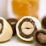 peanut coated with layers of dark and white chocolate revealed by section