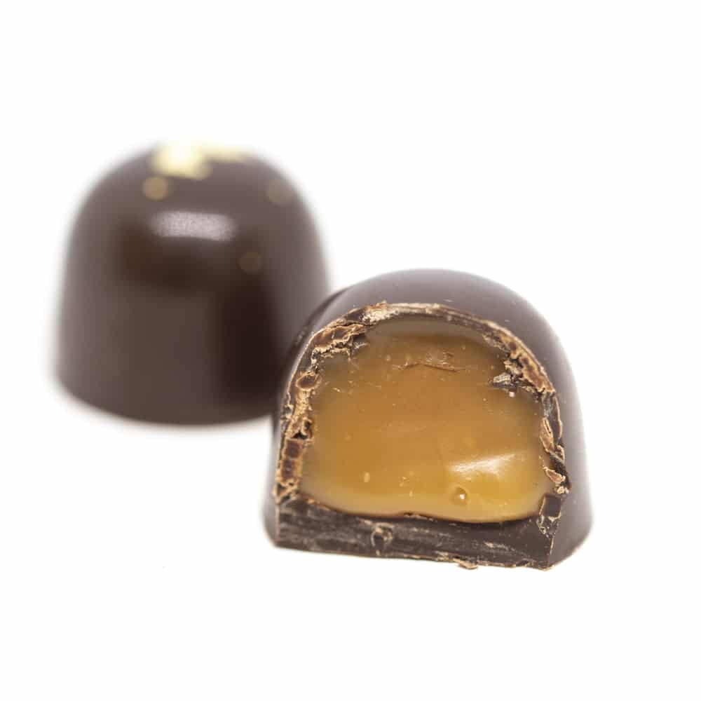 Praline with edible gold foil on white background